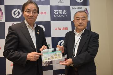 国土地理院の宇田厚生総務部調整官(右)から記念切手を贈られる今泉文彦石岡市長=同市役所