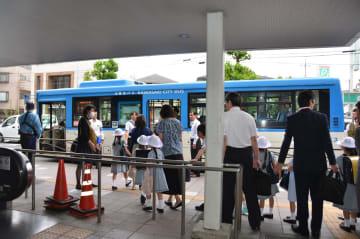 保護者や警察官が見守る中、通学用にチャーターされた市バスに乗り込むカリタス小の児童たち=5日午前7時35分ごろ、川崎市多摩区の登戸駅