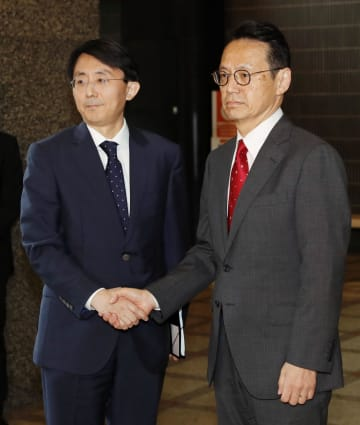 韓国外務省の金丁漢アジア太平洋局長(左)を出迎え、握手する外務省の金杉憲治アジア大洋州局長=5日午前、外務省
