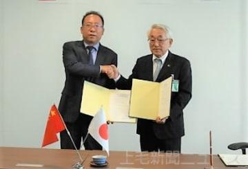 覚書を締結した周書記(左)と横山市長