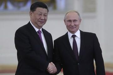 5日、モスクワのクレムリンで会談前に握手するロシアのプーチン大統領(右)と中国の習近平国家主席(タス=共同)