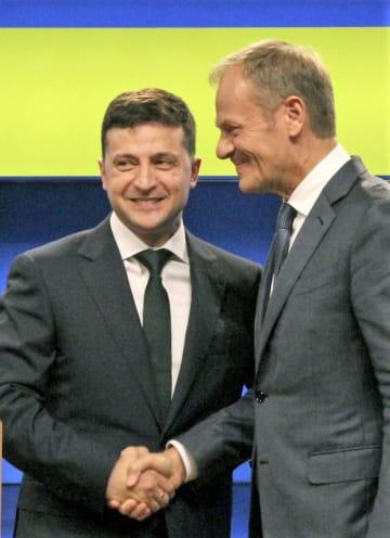 会談後にトゥスクEU大統領(右)と握手を交わすウクライナのゼレンスキー大統領=5日、ブリュッセルのEU本部(共同)