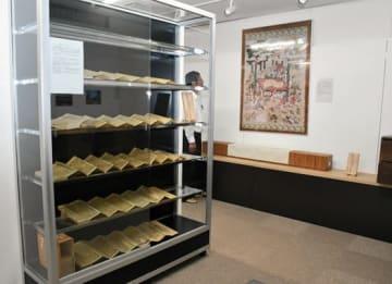 展示されている大般若経。壁にかかる涅槃図の掛け軸は複製品で、16日に実物が「あぜりあ」で一般公開される