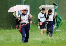 傘や帽子を用意し、悪天候にも万全の準備を怠らない甲南女の上原瑠果(左)=神戸市北区のしあわせの村アーチェリー場