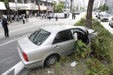 衝突事故で中央分離帯に乗り上げた乗用車。奥は横転したワゴン車=6日午後4時8分、名古屋市中区