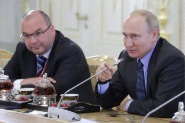 6日、ロシア・サンクトペテルブルクで、各国の主要通信社幹部と会見するプーチン大統領(右)(タス=共同)