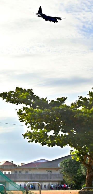 【避難を強いられる生徒ら】サッカーやハンドボールの部活動中、校庭の上空を米軍機が通過。練習の中断を余儀なくされ、建物下へ避難する生徒たち(下)=5日午後5時35分、浦添市当山・浦西中学校(田嶋正雄撮影)