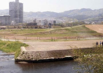 堤防(右端)から徐々に高さが下がる霞堤。増水時はこの部分から遊水地に水を流す(京都府亀岡市篠町)=京都府南丹土木事務所提供