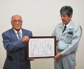 齊藤会長から感謝状を受け取った吉岡常務取締役(右)