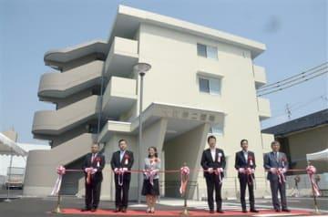 テープカットで大江第二団地の完成を祝う出席者たち=熊本市中央区