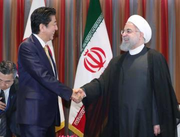 イランのロウハニ大統領(右)と会談前に握手する安倍首相=2018年9月26日、米ニューヨーク(代表撮影・共同)