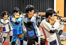 正確な射撃を支える色とりどりのコートに身を包んだ選手たち。鋭いまなざしは小さな的から離れることはなかった=神戸市中央区の神港学園高(撮影・後藤亮平)