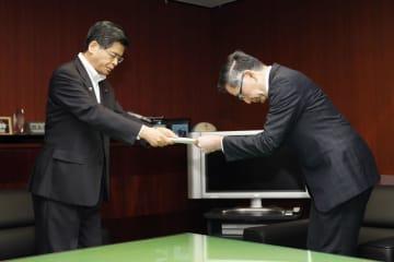 スズキの鈴木俊宏社長(右)に勧告書を手渡す石井国交相=7日午後、東京・霞が関