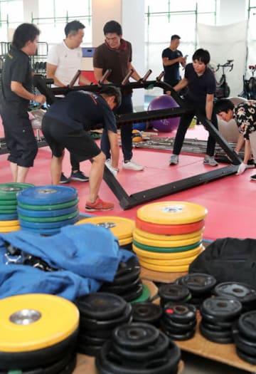 ラグビー日本代表が使用するトレーニング機器の準備をするボランティアら=7日午後、宮崎市・シーガイアスクエア1