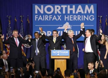 FAIRFAX, VA - NOVEMBER 07: Gov.-elect Ralph Northam (C) links arms with (L-R) current Gov. Terry McAuliffe, Lt. Gov.-elect Justin Fairfax, Attorney General-elect Mark Herring, and U.S. Sen. Mark Warner (D-VA) at an election night rally November...