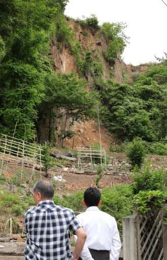 大雨の影響で崩れた崖=7日午後5時43分、広島市南区丹那町(撮影・山崎亮)