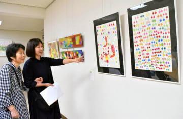 県内の障害者が描いた個性豊かな作品を熱心に鑑賞する来場者=7日午前、松山市道後町2丁目