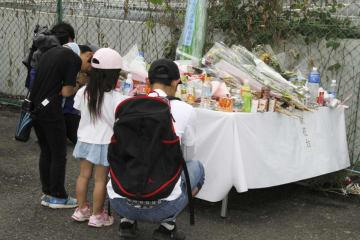 大津市の園児死傷事故から1カ月、現場の献花台前で手を合わせる樫田さん親子=8日午前