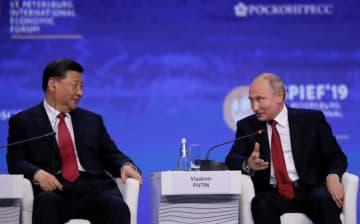 ロシア・サンクトペテルブルクで開かれた国際経済フォーラムに出席する中国の習近平国家主席(左)とロシアのプーチン大統領=7日(ロイター=共同)
