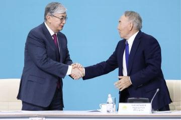 カザフスタン与党ヌル・オタンの臨時党大会で握手するトカエフ大統領(左)とナザルバエフ前大統領=4月23日、ヌルスルタン(タス=共同)