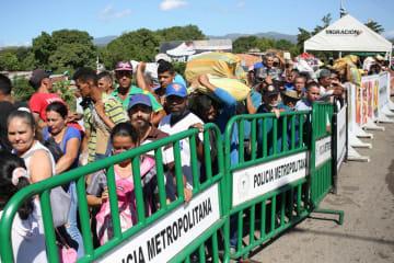 8日、コロンビア、ベネズエラ間の国境を越える人々(ロイター=共同)
