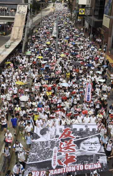 「逃亡犯条例」改正案に反対し、香港中心部をデモ行進する大勢の市民ら=9日(共同)