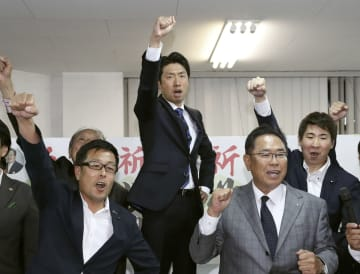 堺市長選で初当選を決め、気勢を上げる大阪維新の会新人の永藤英機氏(中央)=9日夜、堺市
