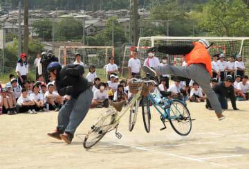 自転車同士の正面衝突事故を再現するスタントマン(大津市北大路3丁目・北大路中)