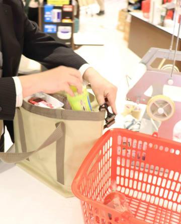 エコバッグに商品を詰め替える記者。店員の温かい言葉も励みになった(17日午後7時20分、京都府亀岡市古世町・亀岡ショッピングセンター・アミティ)