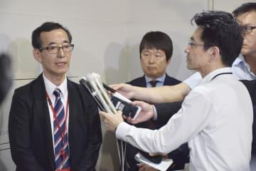 記者団の取材に応じる大阪府泉佐野市の八島弘之副市長(左)=10日午後、総務省