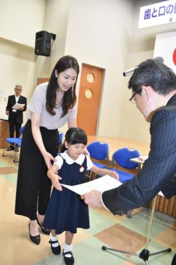 親と子の良い歯のコンクールで最優秀賞を受賞した小倉昌子さん、悠輝香ちゃん親子(左)=9日午前、宮崎市・県歯科医師会館
