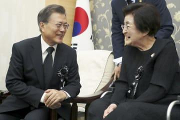 韓国の文在寅大統領(左)と笑顔で言葉を交わす李姫鎬さん=2017年8月、ソウル(聯合=共同)