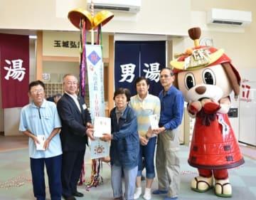 【辻村町長(左から2人目)に祝福される野口さん(右から4人目)ら=玉城町原のふれあいの館で】
