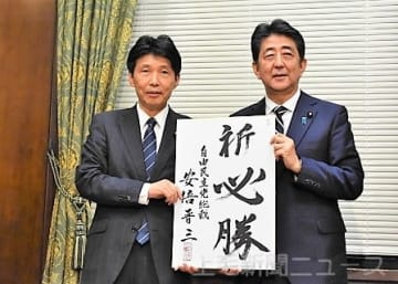 安倍総裁から推薦証とともに激励を受ける山本氏(左)