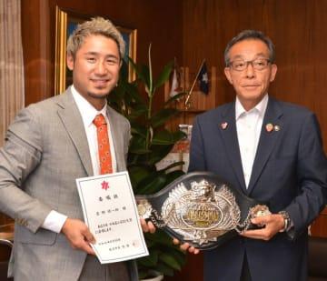 委嘱状を手にする吉野選手(左)。佐藤市長にチャンピオンベルトを披露した