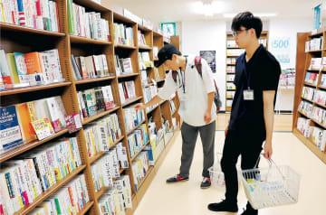 図書館に置いてほしい本を選ぶ学生