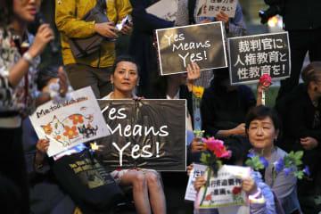 JR東京駅近くで開かれた性暴力に無理解な社会や法制度に抗議する「フラワーデモ」でメッセージを掲げる人たち=11日夜、東京都千代田区