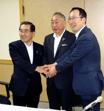 記者会見後、握手を交わす、右から皆川治鶴岡市長、竹内千尋志摩市長、森博幸鹿児島市長=東京・平河町