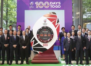 ラグビーW杯日本大会開幕まで100日の記念イベントで披露されたカウントダウン時計と写真に納まる関係者=12日午前、東京都千代田区