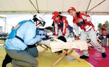 負傷者のけがの状況を確認する救急隊員ら=12日午前10時10分ごろ、仙台市宮城野区の宮城県消防学校