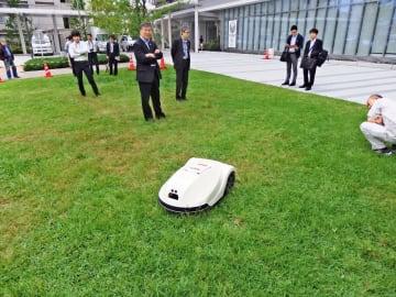 広場をスムーズに走行しながら草を刈っていくロボット=藤沢市役所本庁舎東市民広場