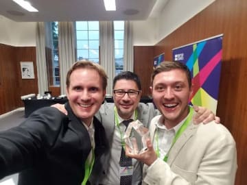 英国ロンドンで開かれた授賞式に出席したクリス・ヴァルヴォ―ナさん(左)と共に教科書制作に携わったマルコス・ベネビデスさん(中央)、ジャック・ヘンリーさん=10日夜(日本時間11日未明)、英国工学技術学会サボイプレイス