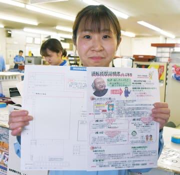 運転経歴証明書交付申請書の案内を持つ南署員