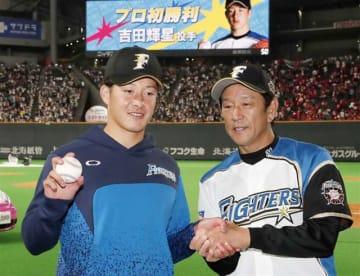 プロ野球交流戦の広島戦で初先発勝利を挙げ、ウイニングボールを手に栗山監督(右)と記念写真に納まる日本ハムの吉田輝星投手=12日、札幌ドーム
