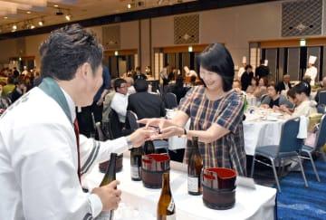 蔵人から笑顔で日本酒が入った冷酒グラスを受け取る来場者=佐賀市のホテルニューオータニ佐賀