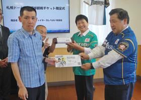 利用者に観戦チケットを手渡す紺谷幹事長(右)と村上会長(中央)