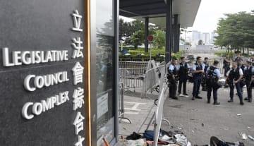 立法会前で警備する警官隊=13日、香港(共同)
