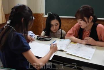 学校の宿題などに取り組む児童(左)と学生ボランティア
