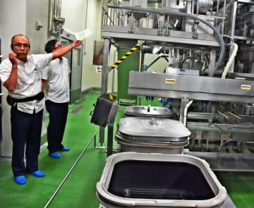 (写図説明)米一粒一粒を均一に加熱できる「踊り炊き」の釜を紹介する武蔵野沖縄工場のスタッフ=11日、浦添市港川
