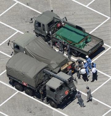 栃木県壬生町の壬生パーキングエリアで自衛隊車両の周辺に集まる自衛隊員ら=13日午後1時5分(共同通信社ヘリから)